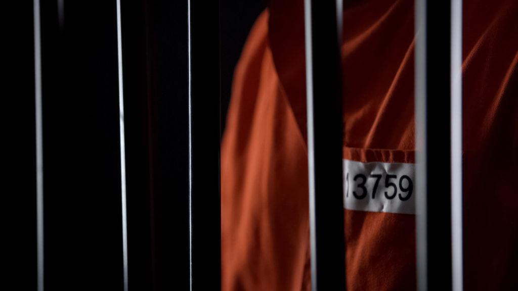 Prisoner in orange behind bars