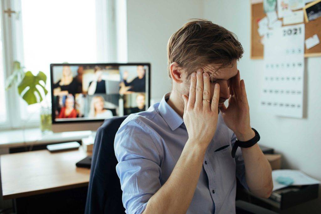 Man looking frustrated with virtual meeting in background.